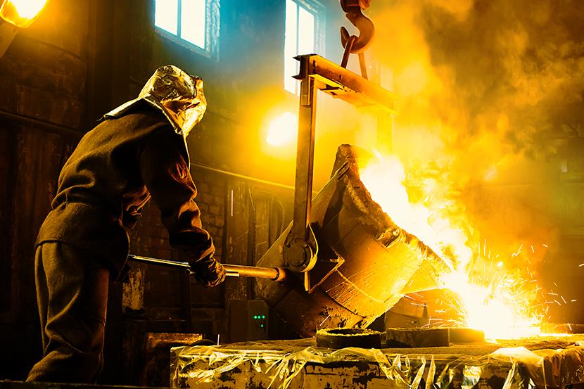 worker pouring molten metal into crucibles