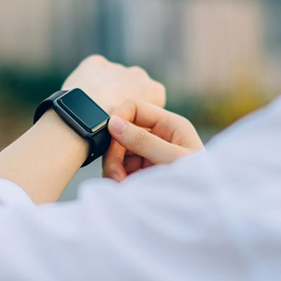 woman in white checking smartwatch on her left wrist