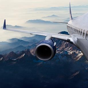 exterior shot of commercial airplane wing and engine flying over mountains