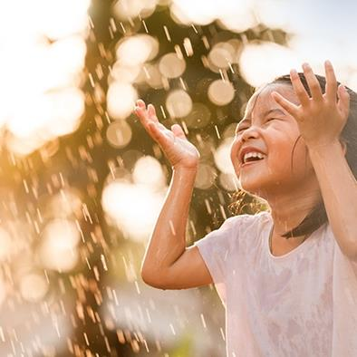 little girl holding hands up and laughing in a sun shower
