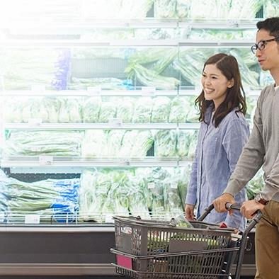 man and woman pushing shopping cart while walking past refrigerated produce section at grocery store