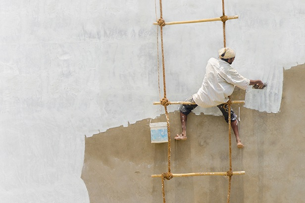 man sitting on rope and bamboo or rattan ladder painting a wall white