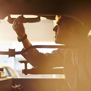 silhouette of mechanic working on underside of car