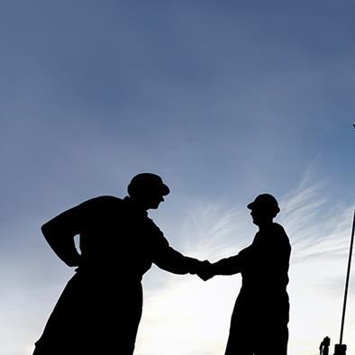 silhouette of two men shaking hands in front of oil machinery