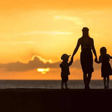 silhouette of woman and two children holding hands at sunset