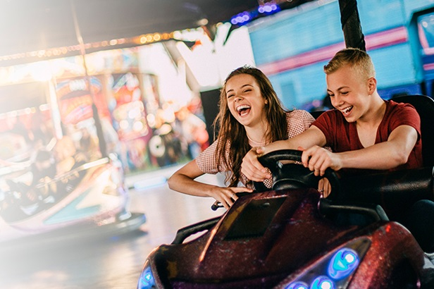smiling boy and girl in a bumper car ride