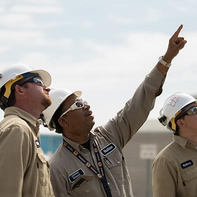three men in white hardhats tan coveralls and sun glasses looking up at something the middle man is