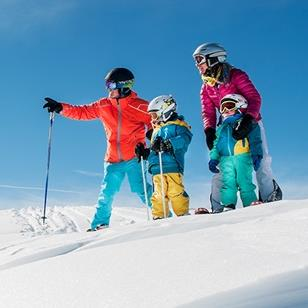 two adults and two children standing at the top of a ski slope
