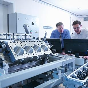 two men looking at computer monitors in a lab or test facilit