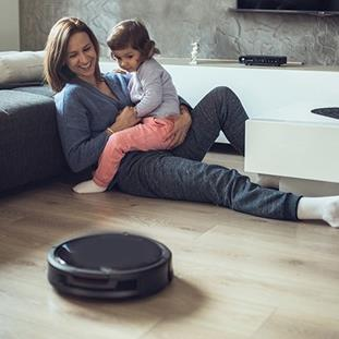 woman holding child on her lap both watching a robot vacuum
