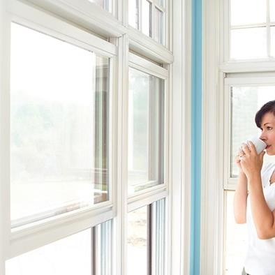 woman holding white mug in both hands looking out bank of windows