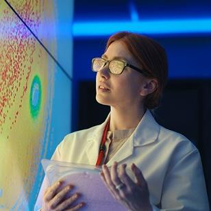 woman in white lab coat holding a silicon wafer in front of a colorful wall
