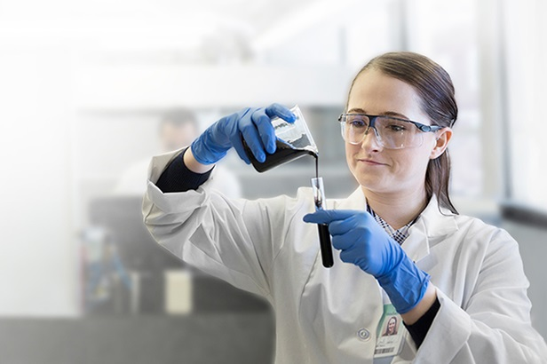 woman in white lab coat pouring liquid from beaker into test tube