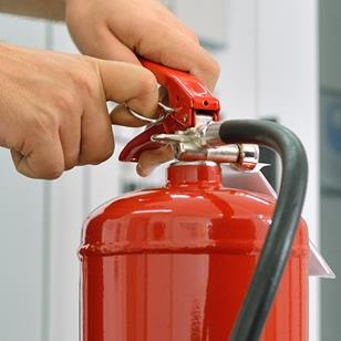 person removing pin from a red fire extinguisher