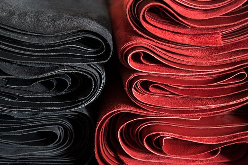 black and red rolls of leather at a tannery