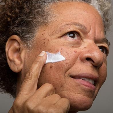 older woman applying cream to face