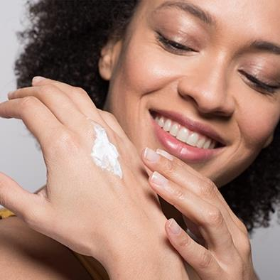 smiling woman putting lotion on her hand