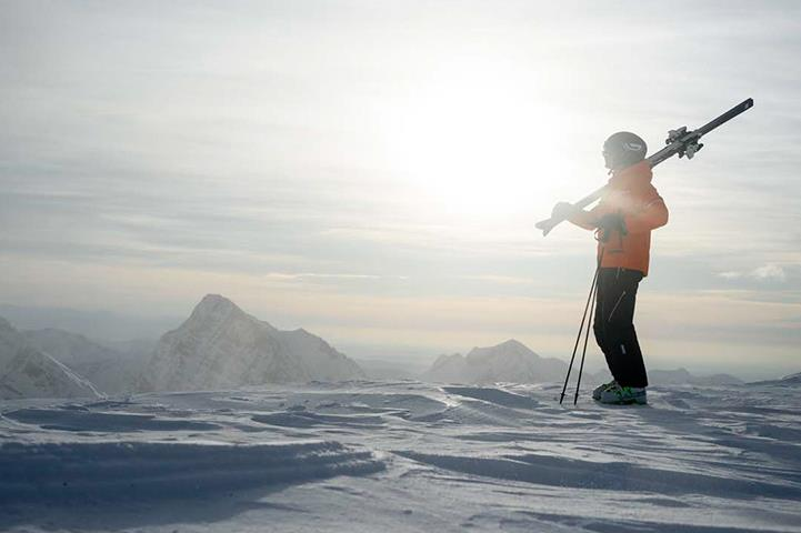skier standing at the top of a snowy mountain