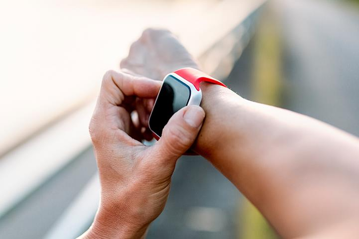 person adjusting smartwatch on right wrist